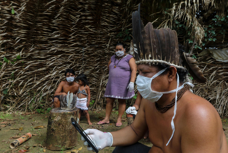Indígenas Sateré-Mawé usan un teléfono móvil para comunicarse con un médico en el estado de Sao Paulo para recibir orientación médica en medio de la pandemia del coronavirus, el 5 de mayo de 2020 en la comunidad Sahu-Ape, 80 km de Manaos, estado de Amazonas, Brasil