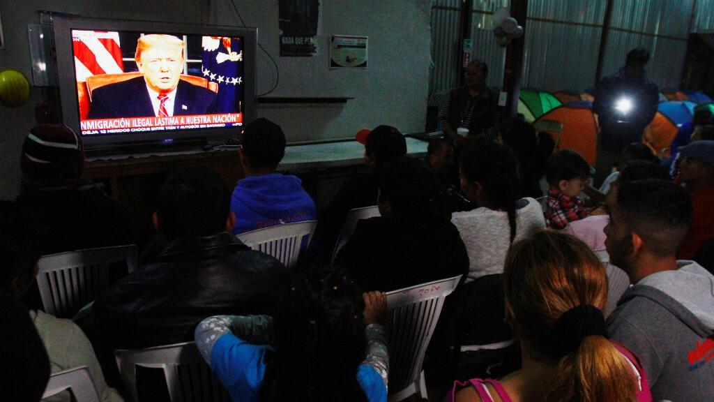 Un grupo de migrantes, integrantes de una caravana de miles de ciudadanos centroamericanos que buscan llegar a Estados Unidos, ven el discurso del presidente Donald Trump sobre la construcción de un muro fronterizo. Tijuana, México, el 8 de enero de 2019.
