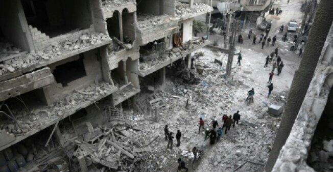 مدنيون أمام الأضرار الناجمة عن غارات لقوات النظام بالغوطة الشرقية المحاصرة (شرق دمشق) في 6 يناير 2018