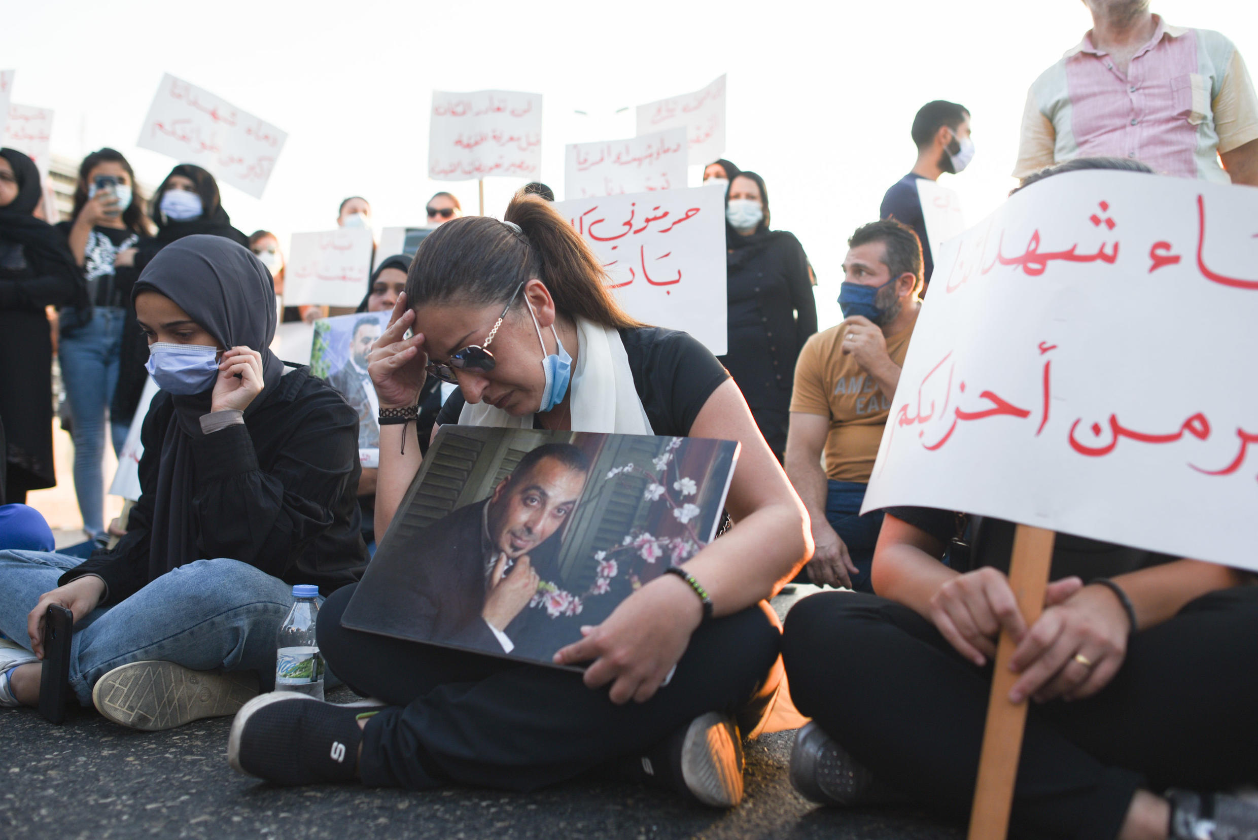 Samia Eido Dohan takes part in a road block with a photo of her husband, Mohamed Nour Doughan, who was killed in the Beirut blast.