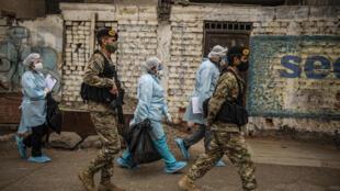 Personal del ministerio de salud de Perú, escoltado por efectivos militares, llega al barrio de Perales, en el distrito de Santa Anita, este de Lima, para realizar un operativo médico casa por casa en medio de la pandemia de covid-19, el 20 de agosto de 2020