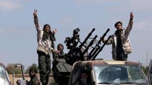Des membres de l'armée nationale libyenne (ANL), commandés par Khalifa Haftar, posent pour une photo alors qu'ils quittent Benghazi pour renforcer les troupes qui se rendent à Tripoli, la capitale libyenne, le 7 avril 2019.
