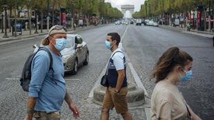 People with face masks cross the Champs Elyseés avenue, with the Arc de Triomphe in background, in Paris, on August 15, 2020.