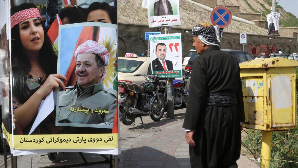Un hombre camina más allá de los carteles de campaña antes de las elecciones parlamentarias en Erbil, Irak, el 6 de mayo de 2018. Fotografía tomada el 6 de mayo de 2018.
