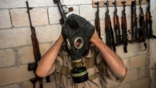 Un combattant rebelle syrien enfile un masque à gaz dans la province d'Idlib.