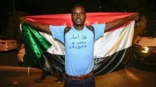 متظاهر سوداني يعبر عن فرحه بسقوط البشير