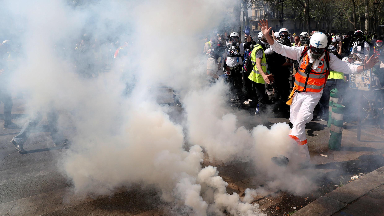 Un médico patea un recipiente de gas lacrimógeno durante una manifestación en el Acto XXIII (la 23ª protesta nacional consecutiva) del movimiento de 'chalecos amarillos', en París, Francia, el 20 de abril de 2019.