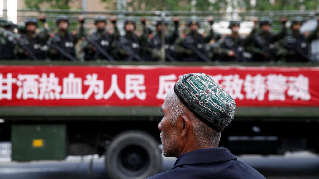 """Imagen de archivo. Un hombre uigur observa un camión que con paramilitares y una pancarta que dice """"Voluntad de derramar sangre para el pueblo. Combatir el terrorismo y combatir a los enemigos es parte del espíritu policial"""". Urumqi, China, el 23 de mayo de 2014."""