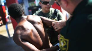 Un agent de la police du comté de Broward interpelle un homme soupçonné d'être sous flakka, le 17 juin 2015.