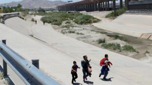 Una familia migrante huye de los miembros de la Guardia Nacional de México, antes de cruzar de forma irregular El Paso, Texas, Estados Unidos, desde Ciudad Juárez, México, el 25 de junio de 2019.