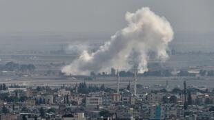 De la fumée s'élève au-dessus de la ville syrienne de Ras al-Aïn, une photo prise depuis la ville turque de Ceylanpinar, le 11octobre2019.