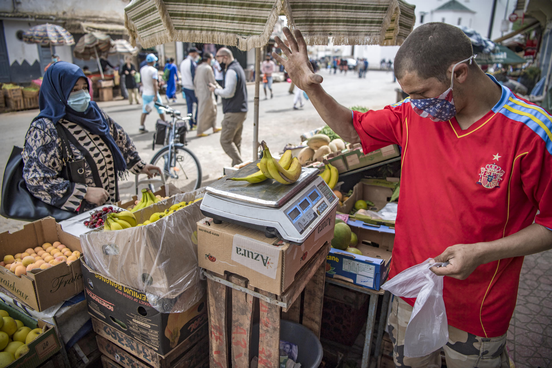 بائع يرتدي قناعًا واقيًا، يزن الموز في السوق المركزي خلال شهر رمضان المبارك في العاصمة المغربية الرباط في 6 أيار/مايو 2020