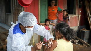 Francisca Gomes da Silva receives the AstraZeneca/Oxford vaccine for the coronavirus disease (COVID-19) by a municipal health worker along the Solimoes river banks, where Ribeirinhos (forest dwellers) live, in Manacapuru, Amazonas state, Brazil, February 1, 2021.