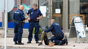 La police finlandaise assiste un homme à terre après l'attaque au couteau perpétrée le 18 août 2017, à Turku.