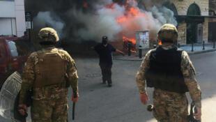 متظاهر أمام مصرف أضرم فيه النار في طرابلس شمال البلاد.
