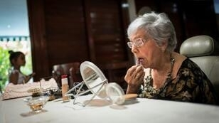 Delia Barroso, 102, applies make-up before her birthday party in Havana - she is one of more than 2,000 centenarians on the island
