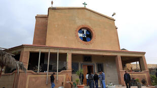 Libyans stand ouside the Coptic church on December 31, 2012, damaged following an explosion last night in the Mediterranean town of Dafinya, just west of Misrata in which two Egyptians were killed