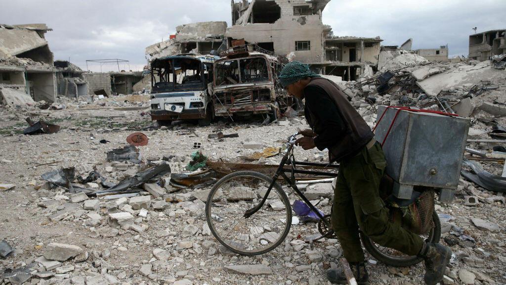 Un hombre camina con su bicicleta en medio de los escombros de la ciudad sitiada de Duma, Guta Oriental, Siria, 30 de marzo de 2018.