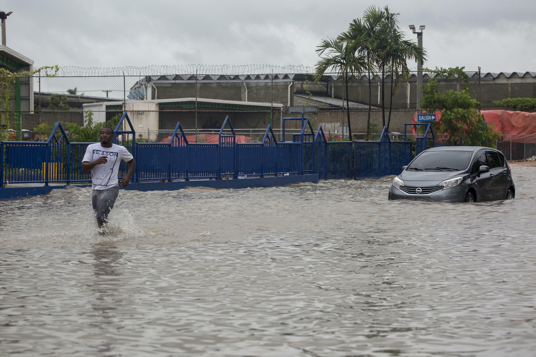Un auto y un hombre transitan por una calle inundada tras el paso de la tormenta tropical Grace en Santo Domingo, el 16 de agosto de 2021