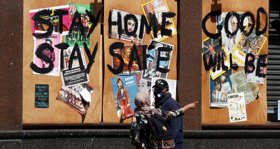 """Dos ciudadanos con mascarillas caminan frente a una casa pública donde hay escrito en una pared un mensaje que dice """"Quédate en casa, quédate sano, Dios será..."""" Londres, Reino Unido, el 22 de mayo de 2020."""