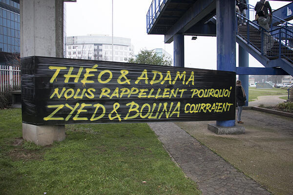 """""""Théo and Adama remind us of why Zyed and Bouna were running,"""" says this poster, referring to the teenagers' death while running away from police in 2005."""