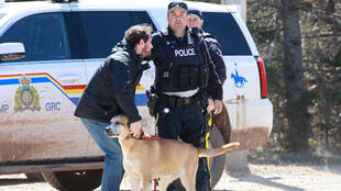 RCMP officer Cedric Landry releases a dog to a man at the checkpoint onto Portapique Beach Road after Gabriel Wortman, a suspected shooter, was taken into custody in Portapique, Nova Scotia, Canada April 19, 2020.