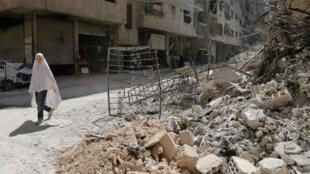 Une Syrienne passe devant des décombres dans une rue de Ein Tarma, dans l'enclave de la Ghouta orientale, près de Damas le 19 juillet.