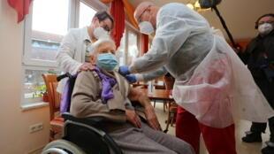 Edith Kwoizalla, 101 ans, reçoit la première dose de vaccin contre le coronavirus à Halberstadt, dans le nord de l'Allemagne le 26 décembre 2020.
