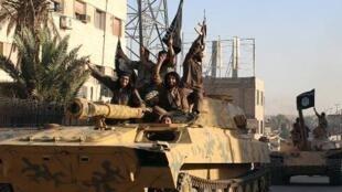 عناصر من تنظيم الدولة الإسلامية يستعرضون في أحد شوارع الرقة في حزيران/ يونيو 2014