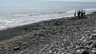 Des policiers inspectent des débris trouvés sur la plage le 2 août 2015 à La Réunion.