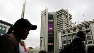 """People walk past an electronic sign on the Bolivia's government building displaying the message """"Stay at home, do it for your family"""" and """"For my community"""", as the coronavirus disease (COVID-19) outbreak continues, in downtown La Paz, Bolivia March 20, 2020."""