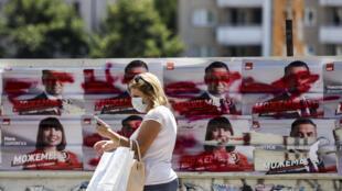 سيدة تمر أمام ملصقات انتخابية في سكوبيي، في 14 تموز/يوليو 2020