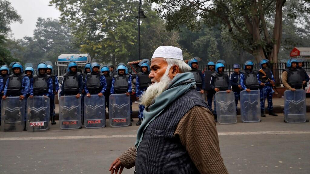 Un hombre musulmán pasa junto al personal de la Fuerza de Acción Rápida durante una protesta contra una nueva ley de ciudadanía, en Delhi, India, el 19 de diciembre de 2019.
