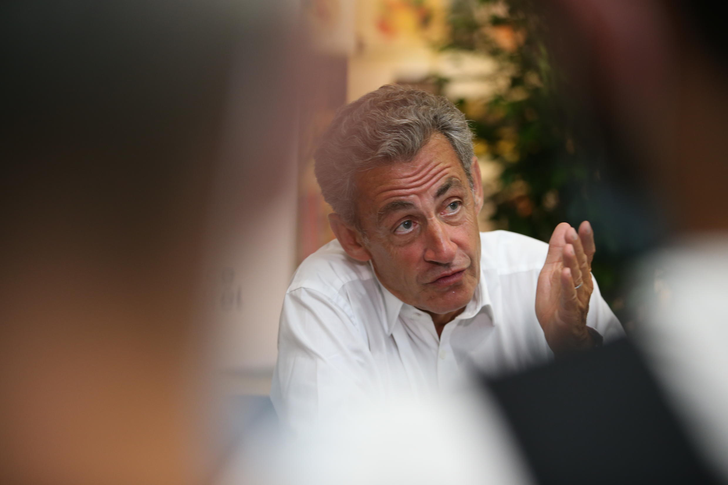 """Former French President Nicolas Sarkozy answers journalist's questions during a signing session of his new book """"Le Temps des Tempêtes"""" inside Baleone shopping center in Ajaccio, on July 24, 2020, on the French Mediterranean island of Corsica."""