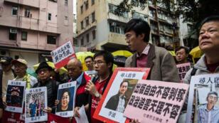 Des manifestants à Hong  Kong dénoncent la disparition de cinq éditeurs critiques à l'égard de Pékin.