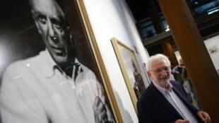 """Lucien Clergue pose devant le portrait du peintre Pablo Picasso en 2013, lors de l'exposition """"Mi amigo Picasso"""" organisée à Madrid, en Espagne."""