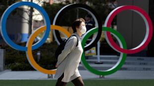 امرأة تمر أمام شعار الألعاب الأولمبية مرتدية كمامة صحية. اليابان