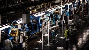 Des employés travaillent le long de la chaîne de montage qui produit à la fois le véhicule électrique Renault Zoe et le véhicule hybride Nissan Micra, à Flins-sur-Seine, le plus grand site de production Renault en France le 6 mai 2020