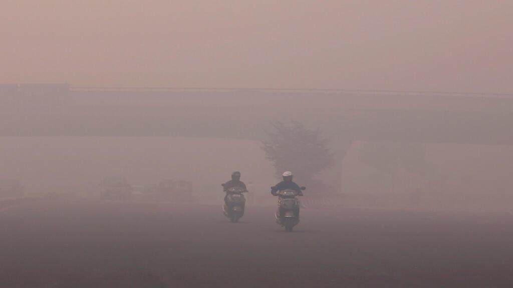 Foto de archivo: Motociclistas se abren paso a través de una nube de smog en Nueva Delhi, India. Octubre 31 del 2016.