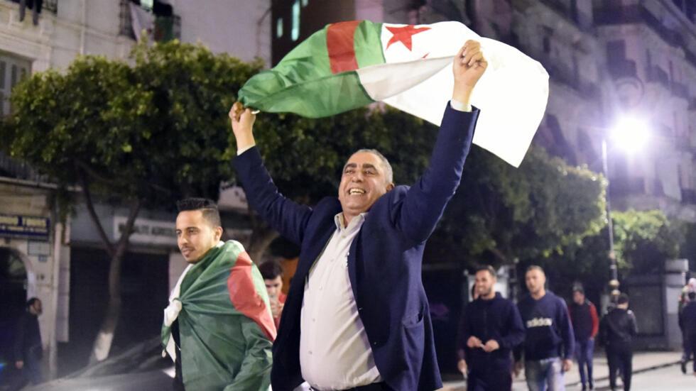 Un homme brandit le drapeau algérien dans les rues d'Alger, juste après que le président Abdelaziz Bouteflika ait remis sa démission au Conseil constitutionnel.