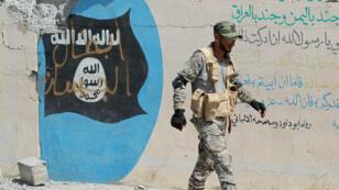 Un soldat irakien passe devant un drapeau de l'organisation de l'État islamique à Sharquat, en Irak.