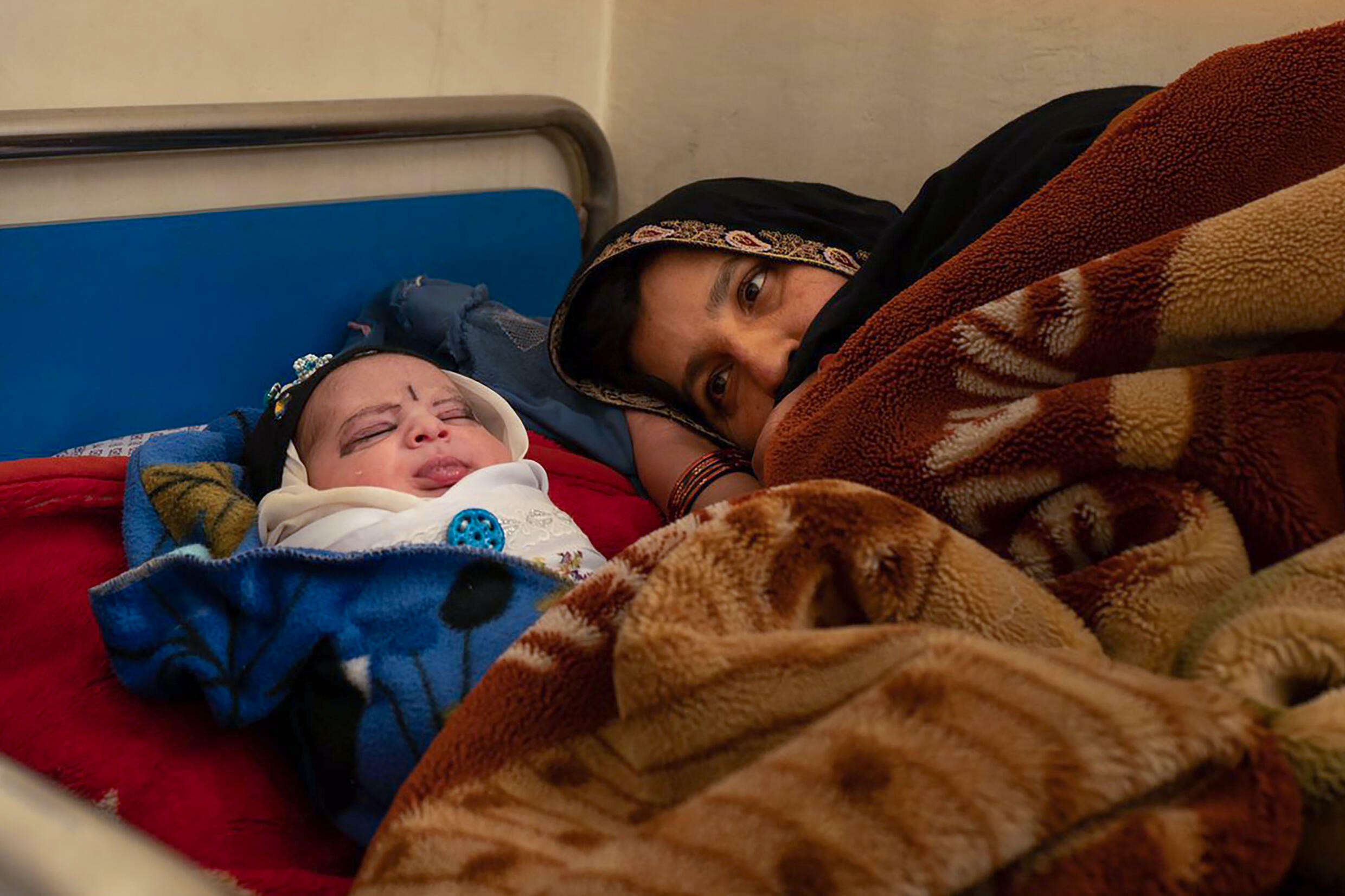 A mother with her newborn rests at the Tangi Saidan clinic