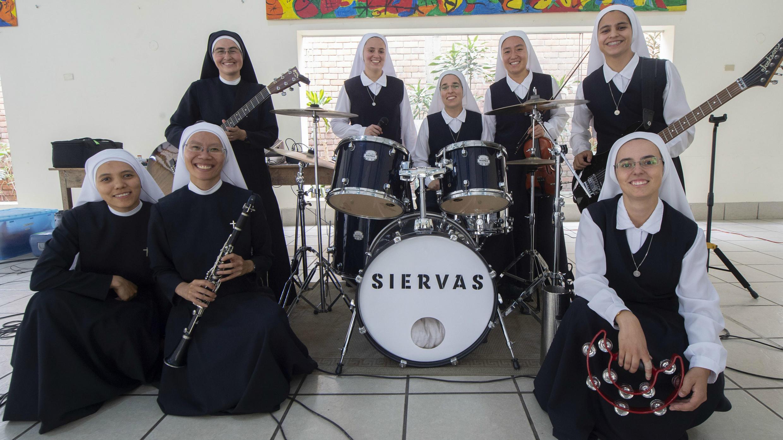 """Ocho de los nueve miembros de la banda de música religiosa """"Las Siervas"""", conocidas como las 'monjas de rock' posan para una foto durante un ensayo en Lima el 14 de enero de 2019."""