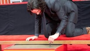 Keanu Reeves signs his name in fresh cement in front of the TCL Chinese Theatre in Los Angeles on May 14, 2019
