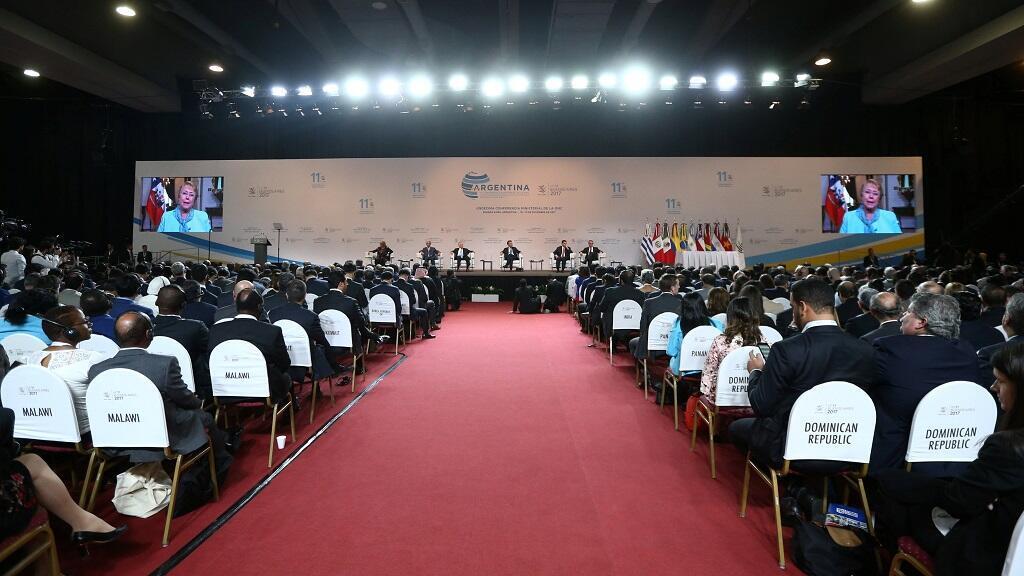 Un video de la presidenta chilena Michelle Bachelet aparece en las pantallas de televisión durante la ceremonia de apertura de la conferencia ministerial de la Organización Mundial del Comercio en Buenos Aires.