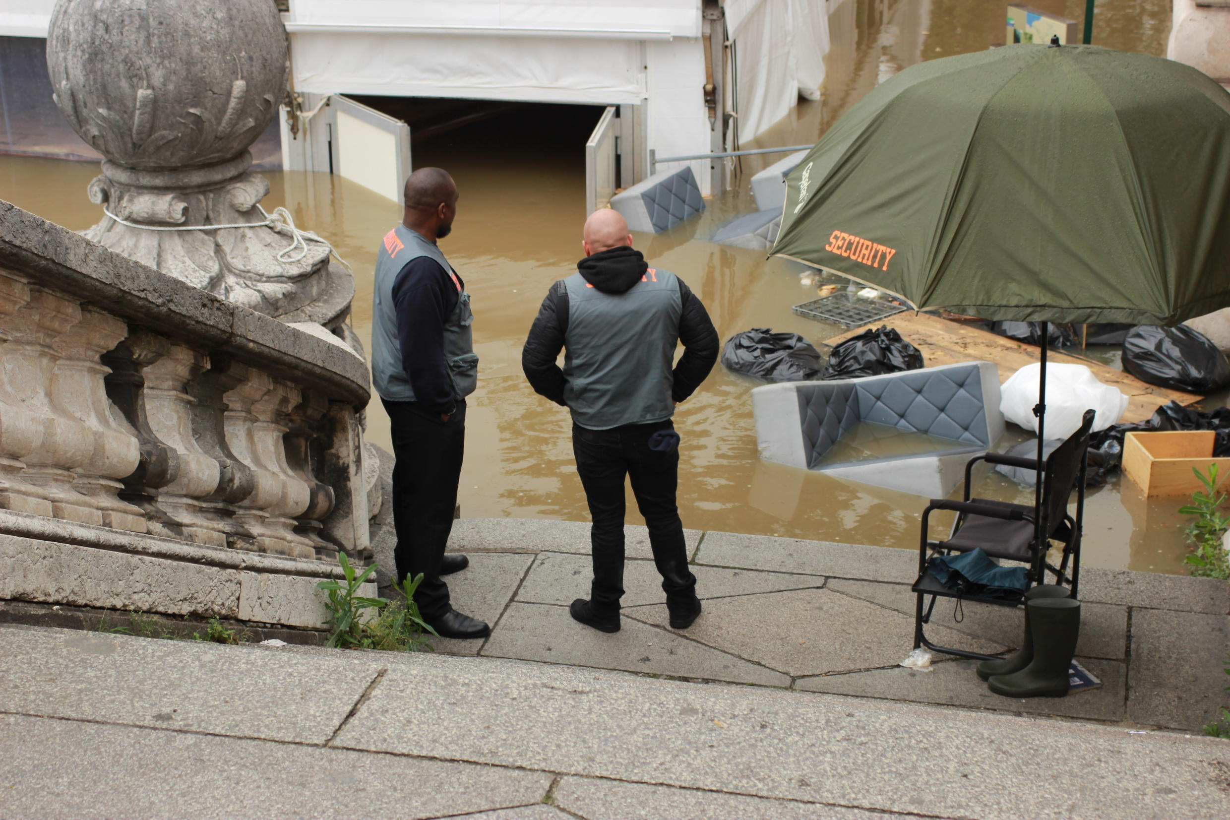 Two security guards look at the furniture that was washed out of a bar-lounge located on the banks of the Seine near the Alexandre III Bridge.