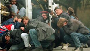 Un soldato bosniaco defiende civiles contra francotiradores serbios durante el asedio de Sarajevo, el 6 de abril del 1992.