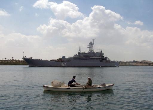مركب صيد يمر أمام سفينة حربية بقناة السويس في 2013