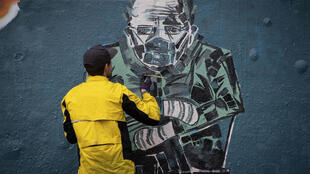Kevin Belyk paints a mural inspired by a photo of US Senator Bernie Sanders bundled up and wearing mittens and a face mask at President Joe Biden's inauguration, on a legal graffiti wall at the Leeside Tunnel skateboard park in Vancouver, British Columbia, on Thursday, January 28, 2021.