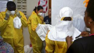 L'équipe de l'association caritative Samaritan's Purse au Liberia, enfilant des tenues de protection, le 24 juillet